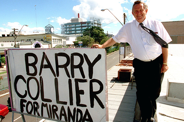 Barry Collier standing on a building rooftop with campaign sign reading