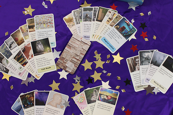 Oracle cards with different genres fanned out on a purple able with shiny starts
