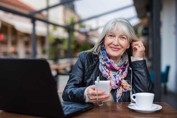 Woman with coffee using mobile phone with earphones