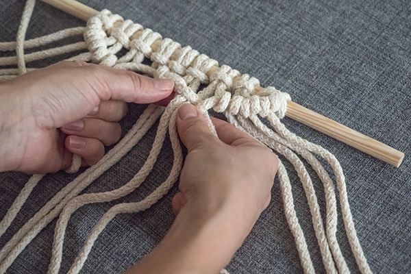 Close up on hands tying macrame