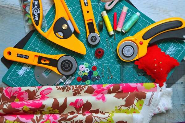 Fabric, thread and rotary cutting tools on cutting mat.