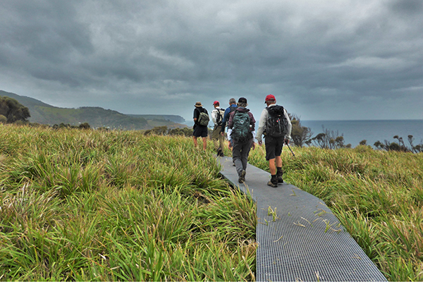 A group of people walking on a track with cliffs, ocean and cloudy sky in background.
