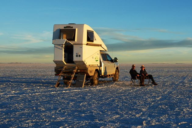 Campervan on ice and two people sitting outside it.