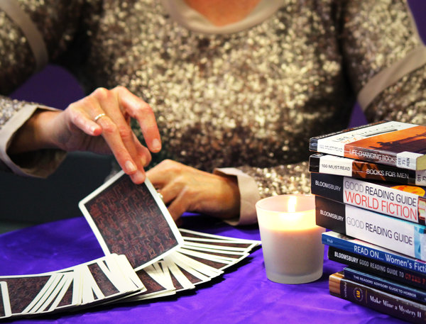 Person drawing out a card from a deck beside a candle and stack of books.