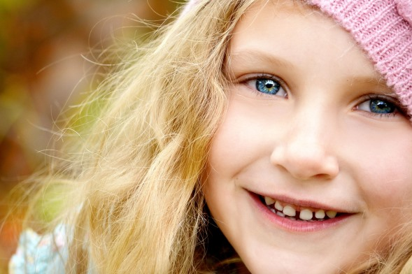 Blonde Primary School Age Girl Smiling with pink beanie.