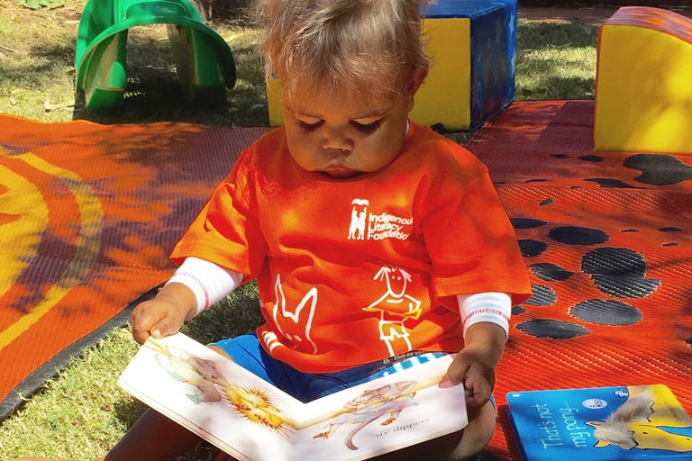 Indigenous toddler reading a book