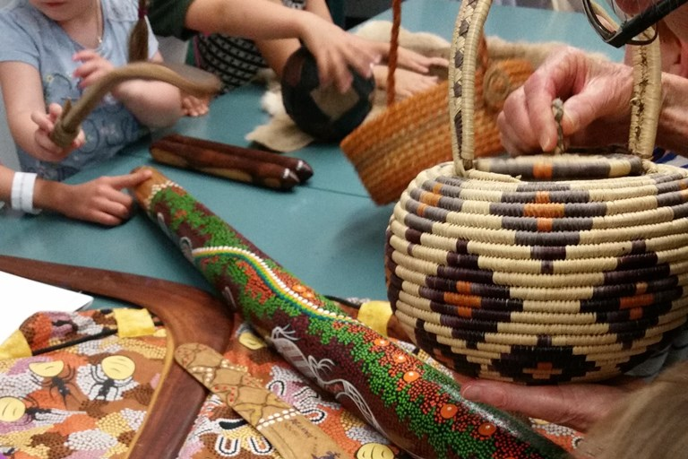 Assortment of Aboriginal items and artwork being held by children.