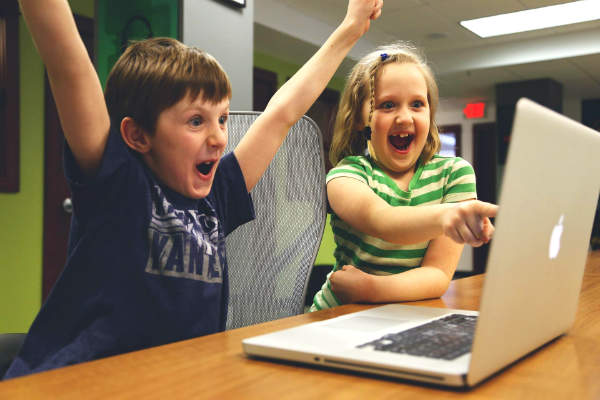 excited boy and girl with computer