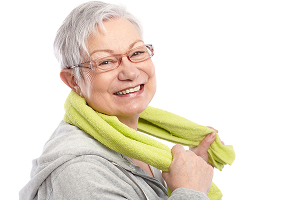Older woman holding a gym towel around her neck smiling at camera
