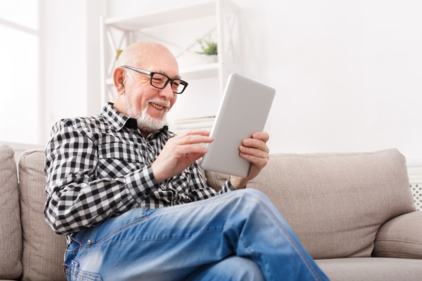 Older man using iPad while sitting on a sofa
