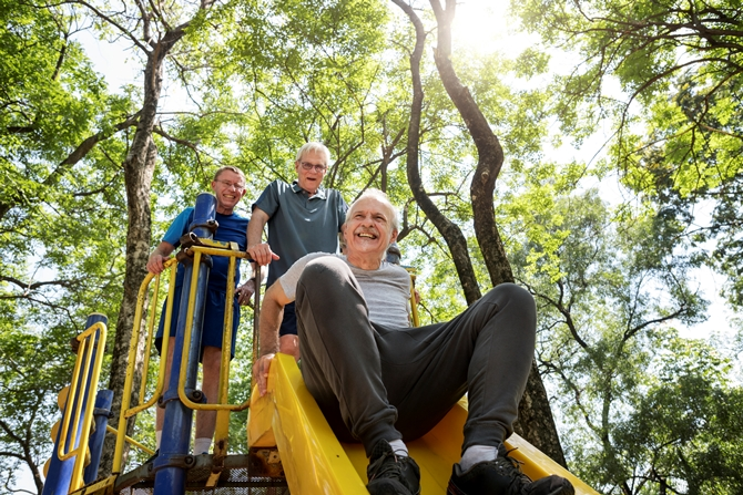 Three older men smiling and laughing on a playground slide.