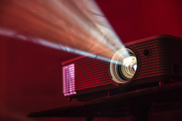 A digital film projector casting light out of lens.