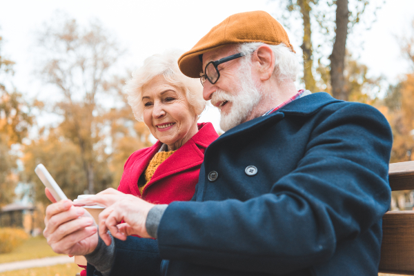 A older man and woman sit on a park bench looking at a smartphone together.