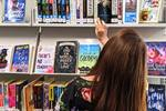 girl browsing the young adult fiction at Sutherland Library