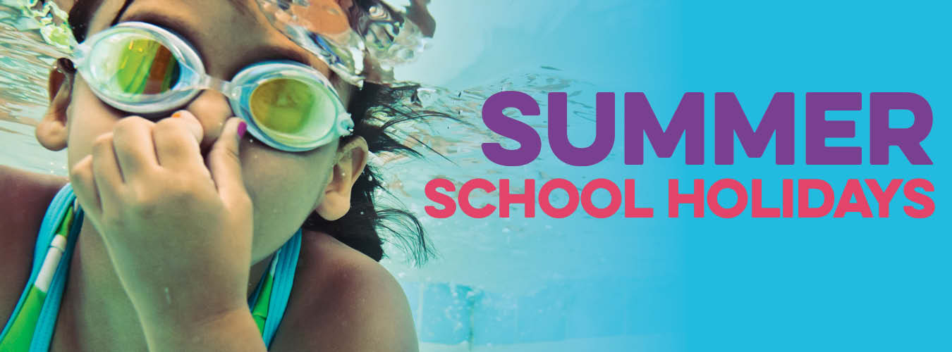 Summer School holidays in Sutherland Shire. Girl with green goggles on and a blue and green swimsuit swimming.
