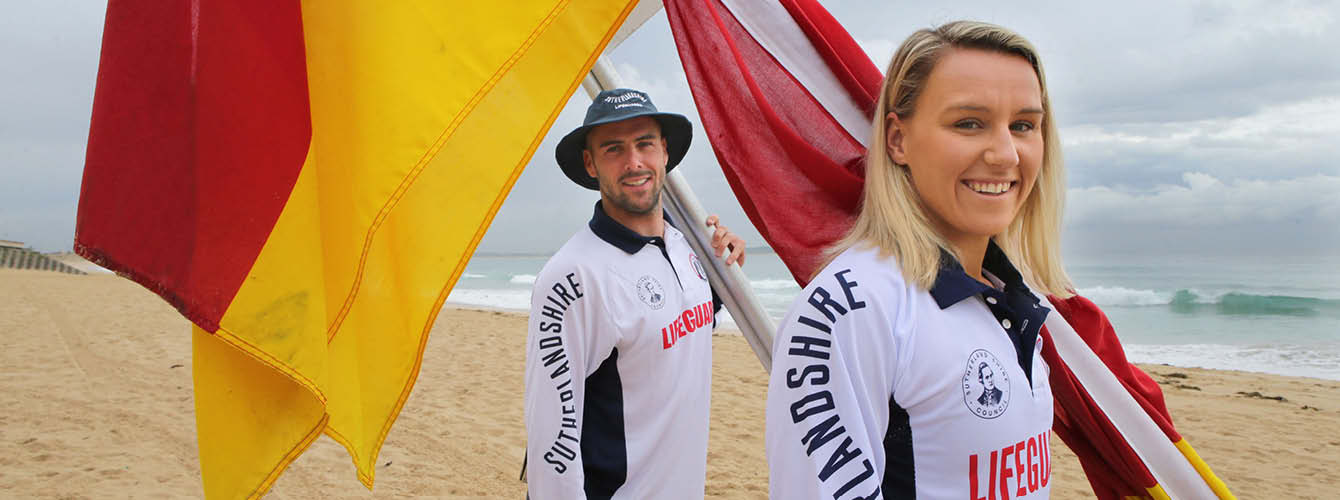Male and Female Lifegaurd on the beach holding the red and yellow flags