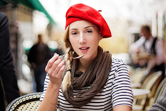 woman at cafe in Paris wearing a red beret