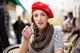 woman at cafe in Pairs wearing a red beret