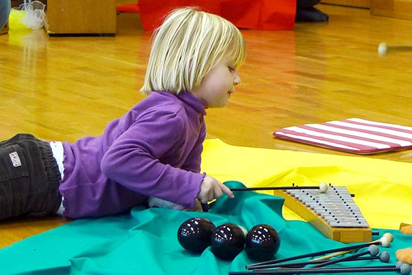 Young girl lying on floor playing a glockenspiel.