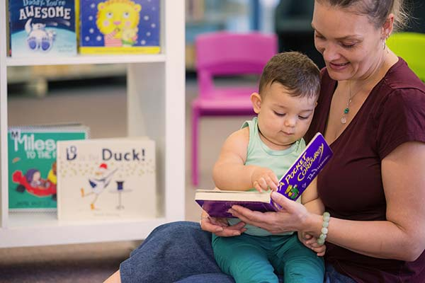 mother reading to baby at the library