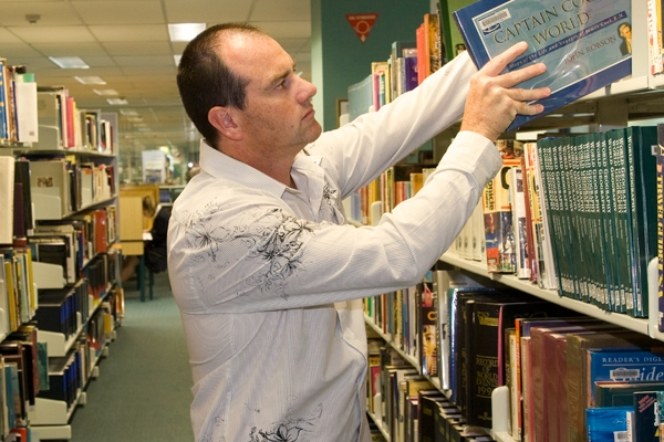 Man browsing shelves at the library