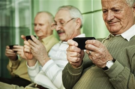Three older men playing with their smartphones