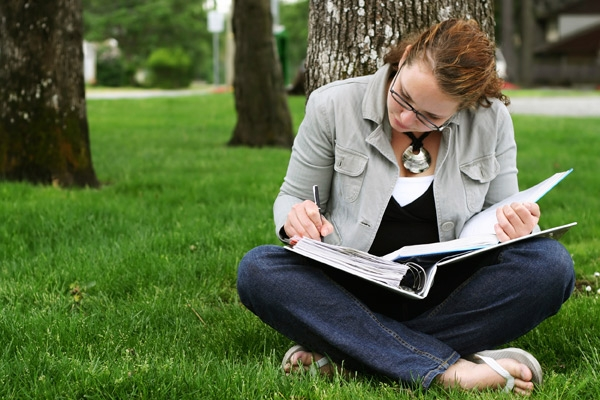 young adult girl studying under a tree